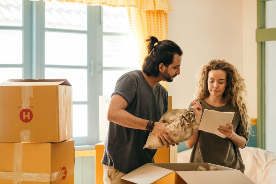 man and woman looking papers while packing